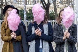three girls eat candy